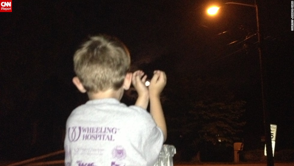 "<a href=""http://ireport.cnn.com/docs/DOC-994146 "">Jennifer Uhrig </a>photographed her son, Hayden, capturing the supermoon outside their home in Wheeling, West Virginia. As a science fan, Hayden talked about the supermoon all weekend, and later in the evening the pair went outside to reach for the moon. ""Ten-thirty is pretty late for us, so it really turned into a giggle session as we tried to get the right shots,"" Uhrig said."
