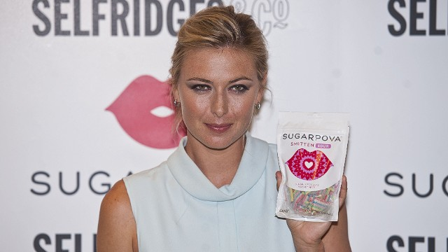 Russian tennis star Maria Sharapova poses with packets of her new candy brand called 'Sugarpova' in Selfridges, central London on June 20, 2013. AFP PHOTO / WILL OLIVERWILL OLIVER/AFP/Getty Images. S023335483