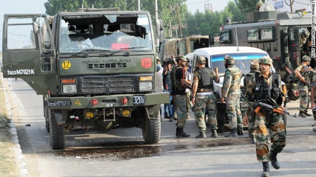 Indian army soldiers stand near a damaged army vehicle at the scene of a deadly attack by militants on the outskirts of Srinagar on June 24, 2013.