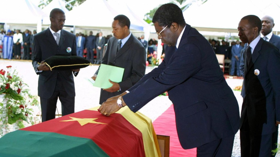 Then Prime Minister Peter Musonge lays a posthumous medal -- the Commander of the National Order of Valor -- on Foe's coffin at his burial in Yaounde.