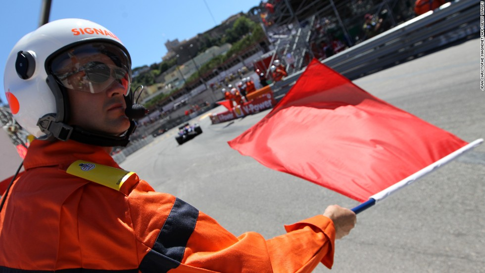Some of the marshals communicate messages from race control to the Formula One drivers. Here a red flag, shown at the Monaco Grand Prix, means the track session has been stopped.