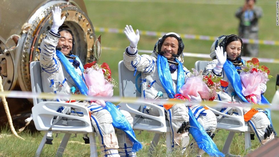 Chinese astronauts Zhang Xiaoguang, Nie Haisheng and Wang Yaping (L-R) wave  in Inner Mongolia after exiting the return capsule of the Shenzhou 10 spacecraft on Wednesday, June 26.