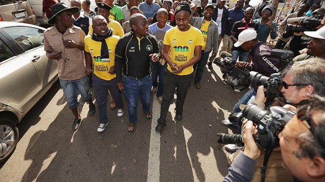 PRETORIA, SOUTH AFRICA - JUNE 27: Members of the ANC Youth League march and sing for former President Nelson Mandela outside the Mediclinic Heart Hospital where Mandela is being treated for a recurring lung infection June 27, 2013 in Pretoria, South Africa. Family members and President Jacob Zuma have visited Mandela in the hospital today. (Photo by Chip Somodevilla/Getty Images)