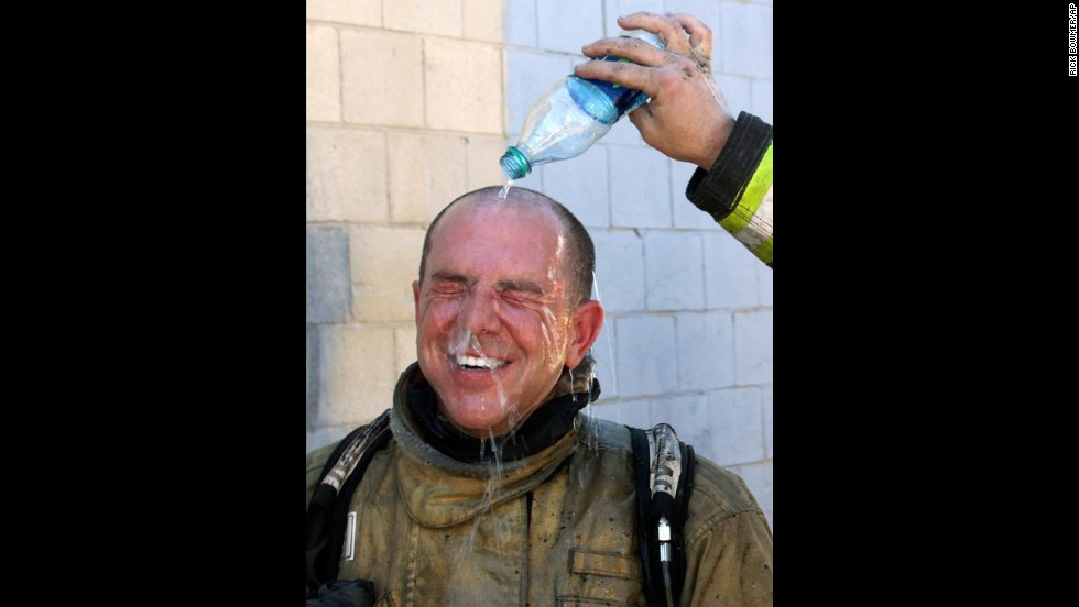 A Salt Lake City fireman pours water over the head of fireman Cary Turner after battling a house fire on Wednesday, June 26. Temperatures in Utah are approaching record highs.