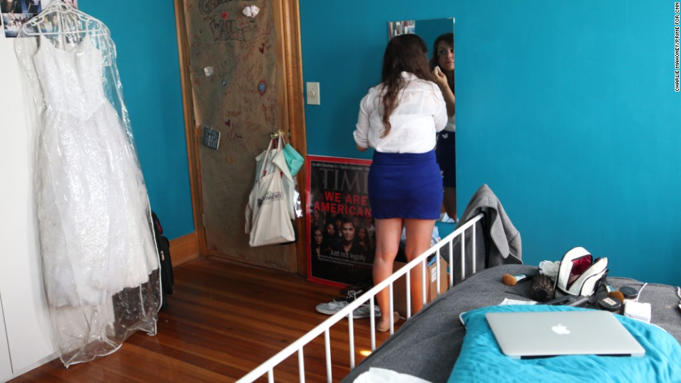 Renata prepares for her day by applying makeup in her room in her Boston apartment.