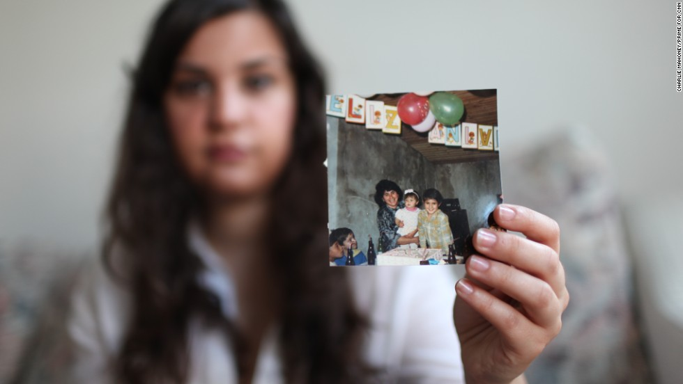 Renata shows a photo of her with her brother and mother during a birthday party prior to her arrival in the United States.
