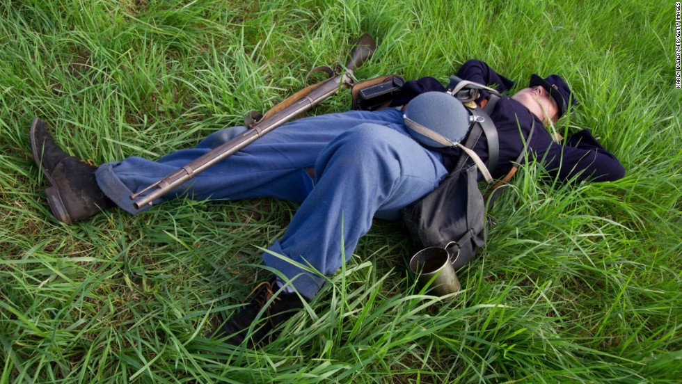 A Union infantryman lies on the ground during a reenactment in Gettysburg on Friday, June 28.