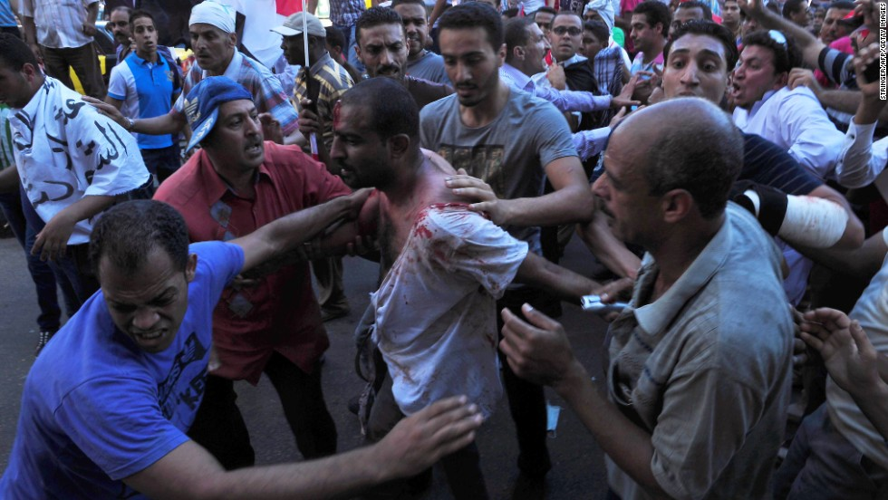 Egyptians help a wounded man following clashes between Morsy's supporters and opponents in Alexandria on June 28.