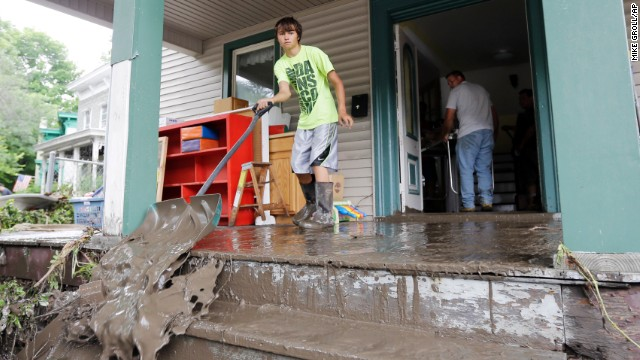 Brendan Hazzard shovels mud from a friend's flood-damaged home on Friday, June 28, in Fort Plain, New York.