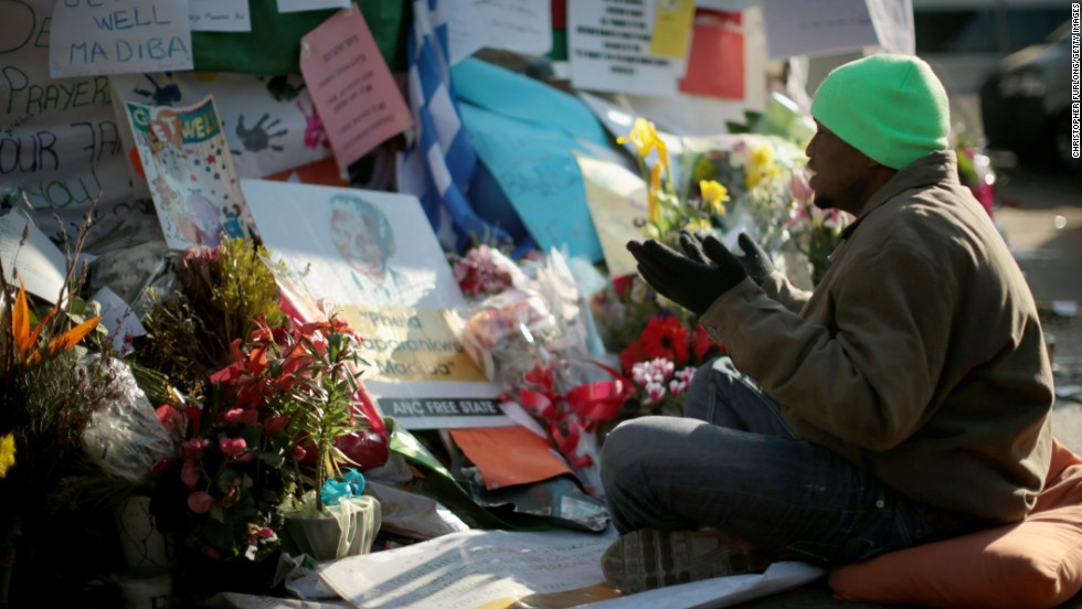 A man prays at the tribute wall for Mandela outside the hospital on June 30.