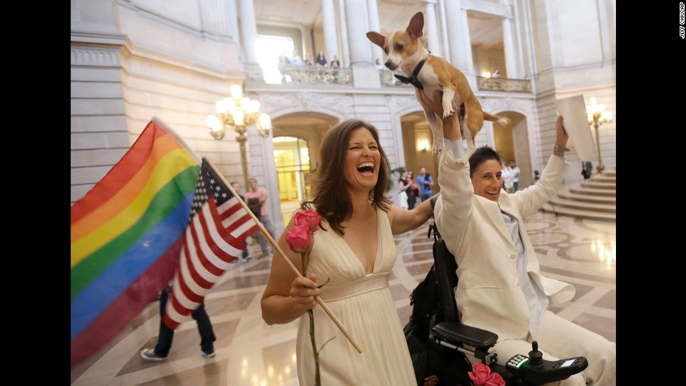 Jen Rainin, left, laughs as her wife, Frances Stevens, holds up their dog, Punum, after they were married in San Fransisco on June 28.