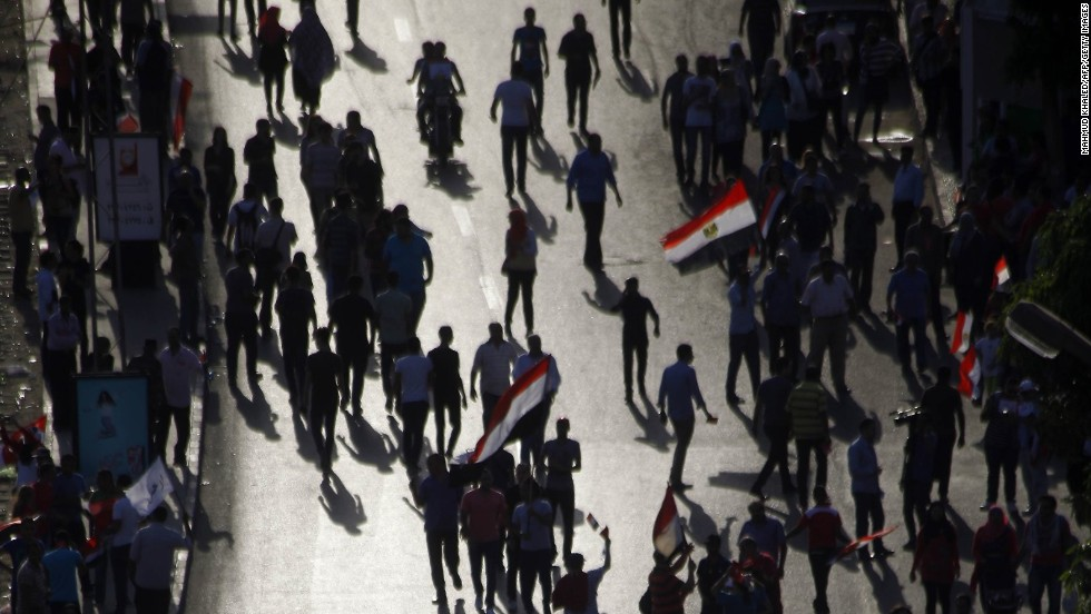 "JULY 1 - CAIRO, EGYPT: Opponents of Egypt's Islamist President Mohamed Morsy <a href=""http://cnn.com/2013/06/30/world/africa/egypt-protests/index.html"">gather for a protest outside the presidential palace in Cairo</a>, calling for Morsy to step down. Egyptians who helped overthrow a 29-year dictatorship in a widely-hailed revolution have now given the country's first democratically elected president <a href=""http://cnn.com/2013/07/01/world/meast/egypt-protests/index.html"">one day to resign</a>."