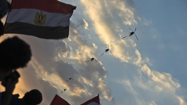 Egyptian army helicopters fly over as hundreds of thousands of Egyptian demonstrators gather outside the presidential palace in Cairo during a protest calling for the ouster of President Mohamed Morsi on July 1, 2013. Egypt's armed forces warned that it will intervene if the people's demands are not met within 48 hours, after millions took to the streets to demand the resignation of Morsi. TOPSHOTS/AFP PHOTO/KHALED DESOUKIKHALED DESOUKI/AFP/Getty Images