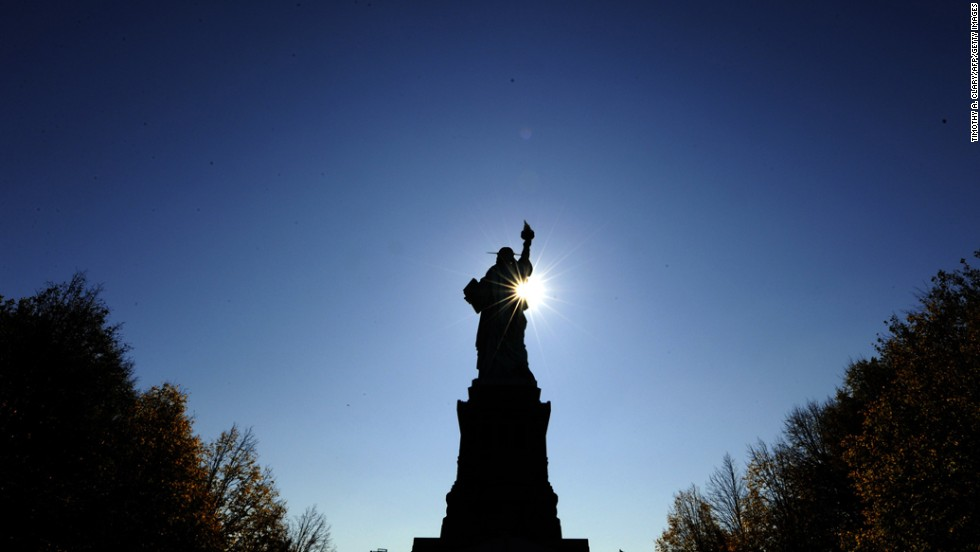 The sun rises in front of the Statue of Liberty before the start of ceremonies on October 28, 2011.