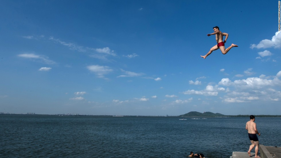 A man jumps into East Lake in Wuhan, the capital of central China's Hubei Province, on Wednesday, July 3.