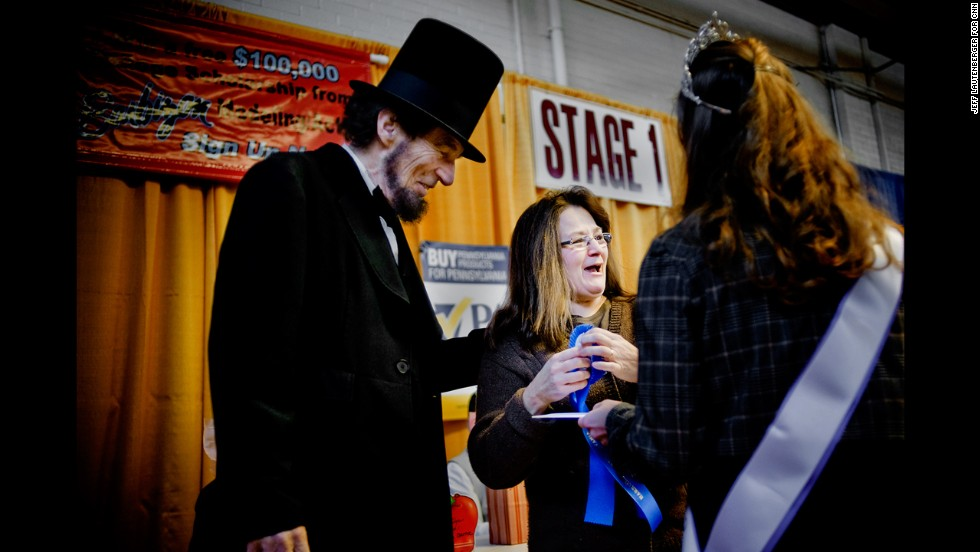 An Abraham Lincoln impersonator awards Lorrie Rauch of Lynn Township, Pennsylvania, a first place ribbon for best apple pie at the 2013 Pennsylvania Farm Show on January 1, in Harrisburg, Pennsylvania.