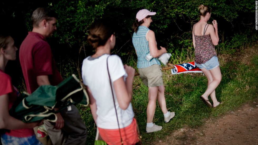 Spectators carry a Confederate flag back to the parking lot on July 2, at the re-enactment of the Battle of Hanover, which took place just before the Gettysburg battle.