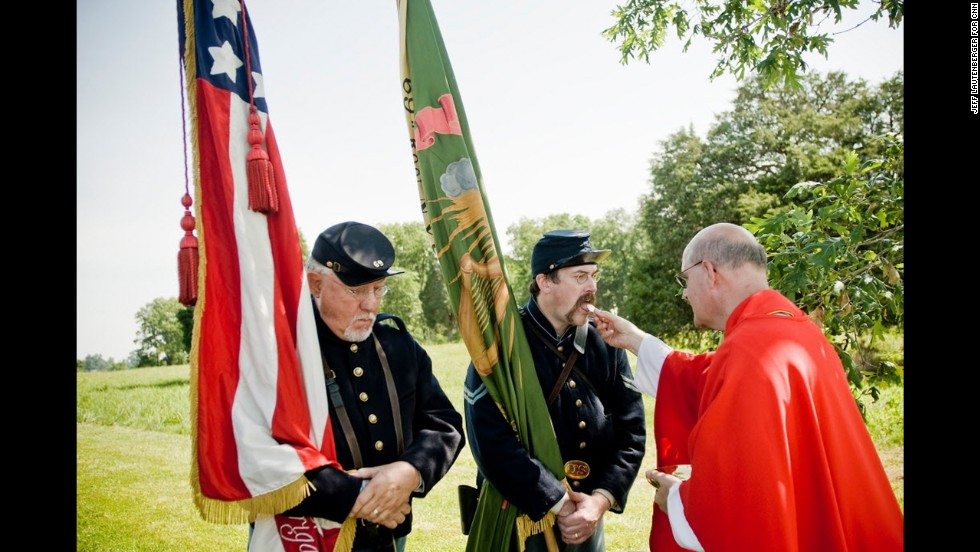 The Rev. Michael Reid gives Holy Communion to Irish Brigade re-enactors Pat Gaughan, center, and Gary Ryan, during a battlefield Mass at Gettysburg National Military Park on June 22.