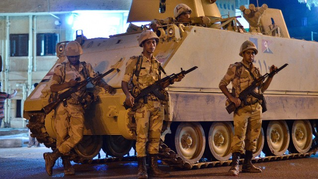 Egyptian Army soldiers patrol the streets outside Cairo University after a broadcast confirming that the army will temporarily be taking over from the country's first democratically elected president Mohamed Morsy on July 3, 2013 in Cairo.