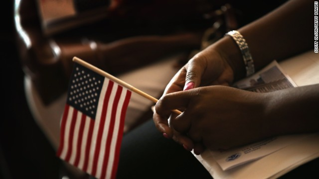 A new U.S. citizen holds a flag July 3 along with her citizenship papers. Would-be citizens must pass a civics and history test.