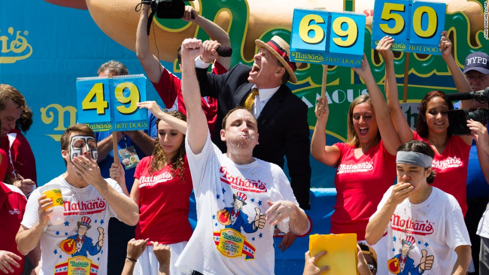 "Perennial chomping champ Joey Chestnut, center, wins <a href=""http://www.cnn.com/2013/07/04/us/ny-hot-dog-contest/index.html"">New York's annual Independence Day hot dog eating competition</a> yet again with a total of 69 hot dogs and buns on Thursday at Coney Island in Brooklyn."