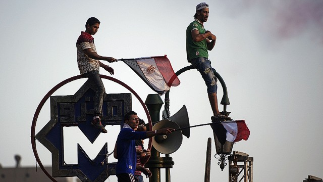 "Egyptians wave the national flag atop of the metro sign in Egypt's landmark Tahrir square on July 4, 2013. Egypt's Muslim Brotherhood, from which ousted president Mohamed Morsi hails, denounced a new ""police state"" after the arrest of Islamist leaders and the closure of satellite channels. AFP PHOTO/GIANLUIGI GUERCIAGIANLUIGI GUERCIA/AFP/Getty Images"