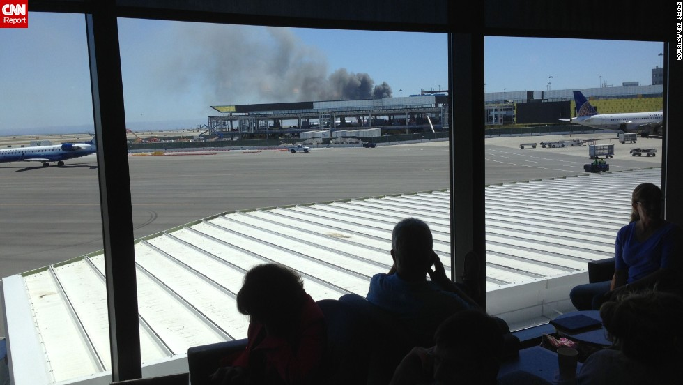 iReporter Val Vaden captured this photo while waiting in a departure lounge at the San Francisco airport on July 6. Val observed the billowing smoke and emergency responders' rush in.