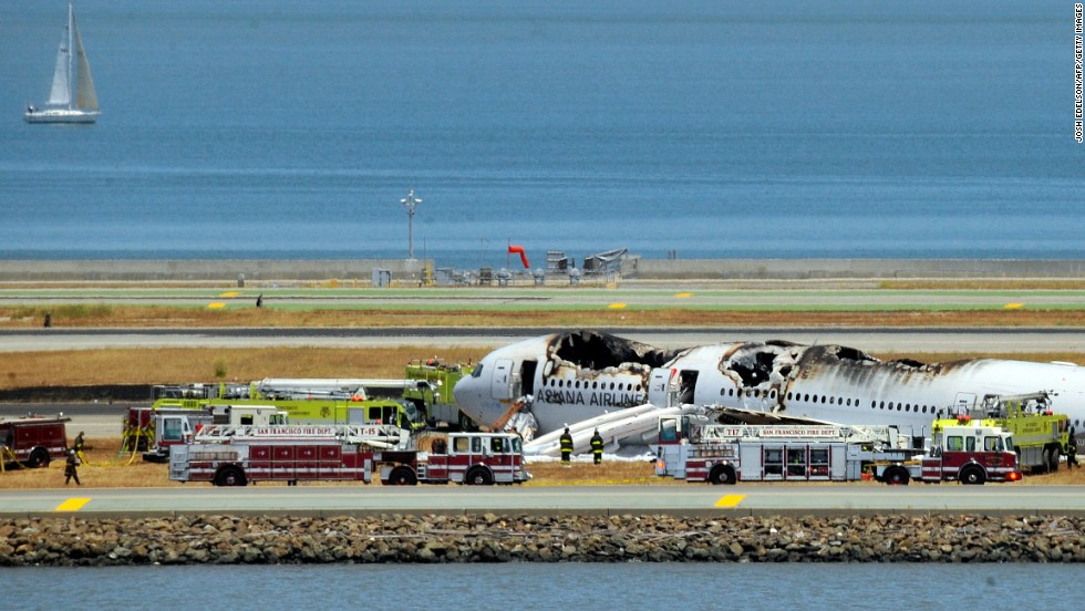 The burned-out plane sits surrounded by emergency vehicles on July 6.