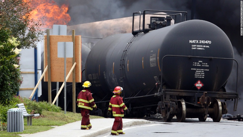 Firefighters walk past derailed cars on July 6.