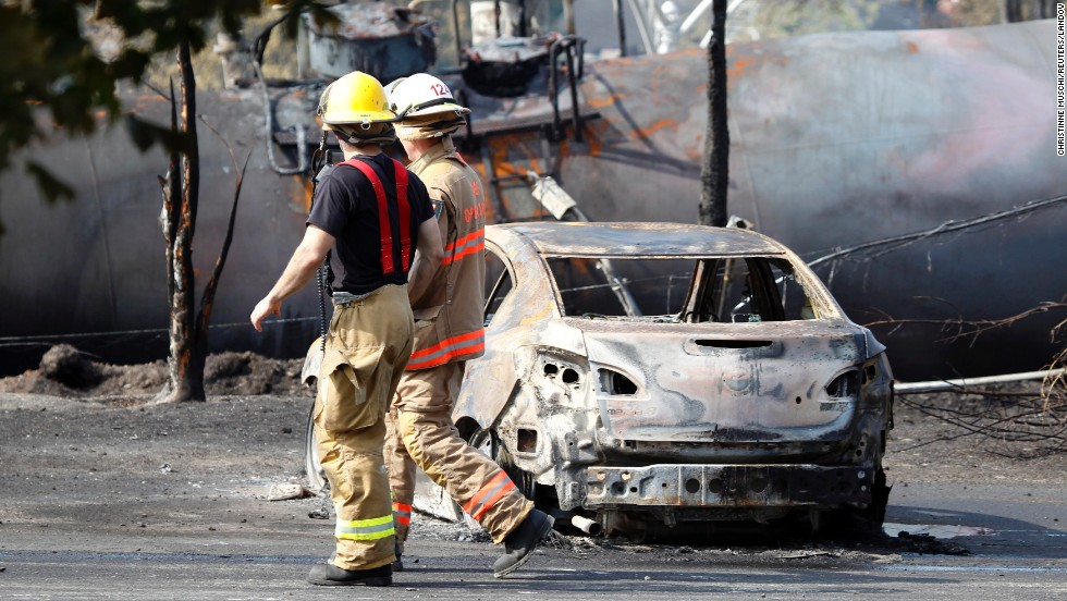 Firefighters walk past a burnt out vehicle near the train derailment in Lac Megantic, Quebec, July 7.