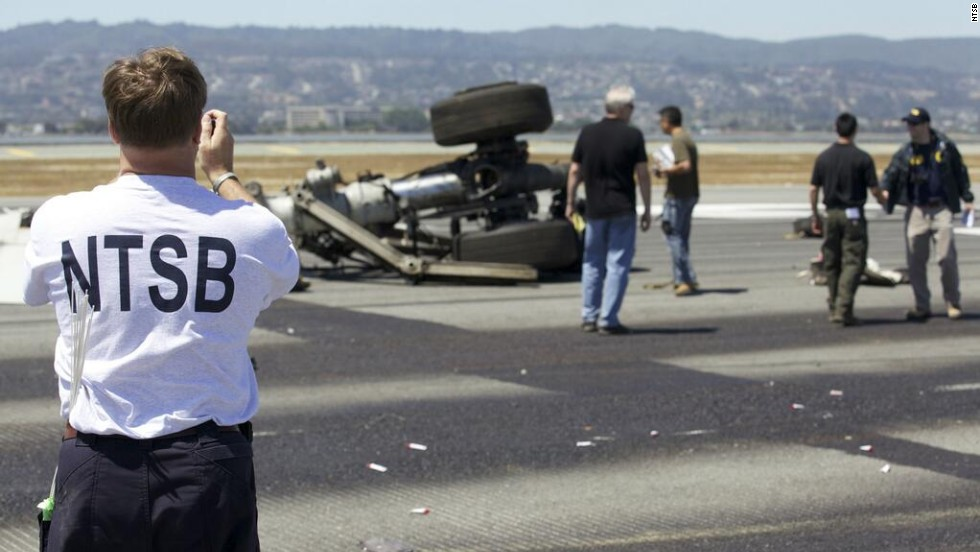 An investigator photographs part of the landing gear at the crash site in a handout released on July 7. Investigators believe that the pilots were flying too slow and too low as they neared the airport on July 6.