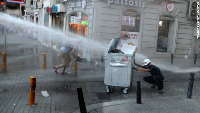 A protestor take cover from water cannon during clashes with police officers on Istiklal avenue, in Istanbul on July 8, 2013. Turkish riot police fired rubber bullets, tear gas and water cannon to block demonstrators from entering a small Istanbul park, the birthplace of deadly unrest that engulfed the country last month. AFP PHOTO/BULENT KILIC (Photo credit should read BULENT KILIC/AFP/Getty Images)