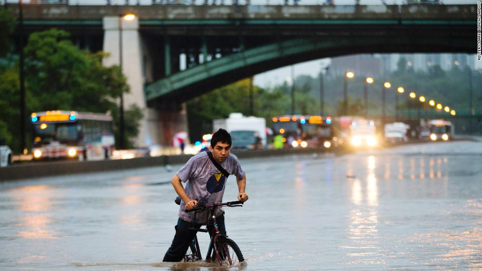 A biker struggles through the waters on the Don Valley Parkway on July 8.