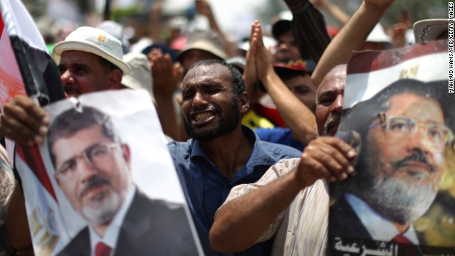 Egyptian supporters of deposed president Mohamed Morsi (portrait) shout slogans during a rally in support of the former Islamist leader outside Cairo's Rabaa al-Adawiya mosque on July 9, 2013. Egypt's interim leader vowed fresh elections by early next year as Islamists staged fresh rallies after dozens of Morsi's loyalists died in clashes at a Cairo military barracks.