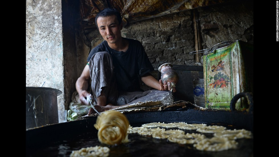 A man cook sweets in Kabul on July 8.