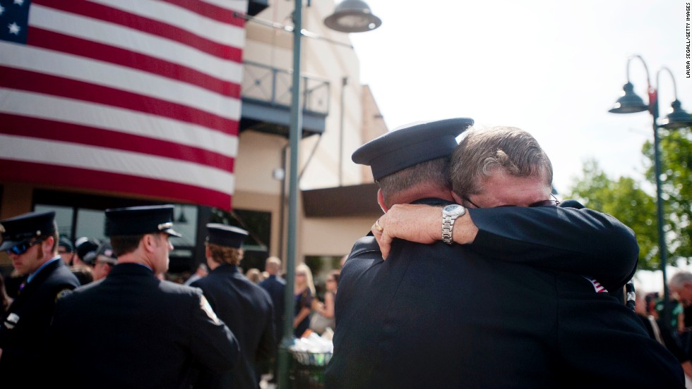 Chaplain Bob Ossler, right, hugs people at the Prescott Valley, Arizona, memorial service on July 9, honoring the fallen firefighters of the Yarnell Hill Fire.