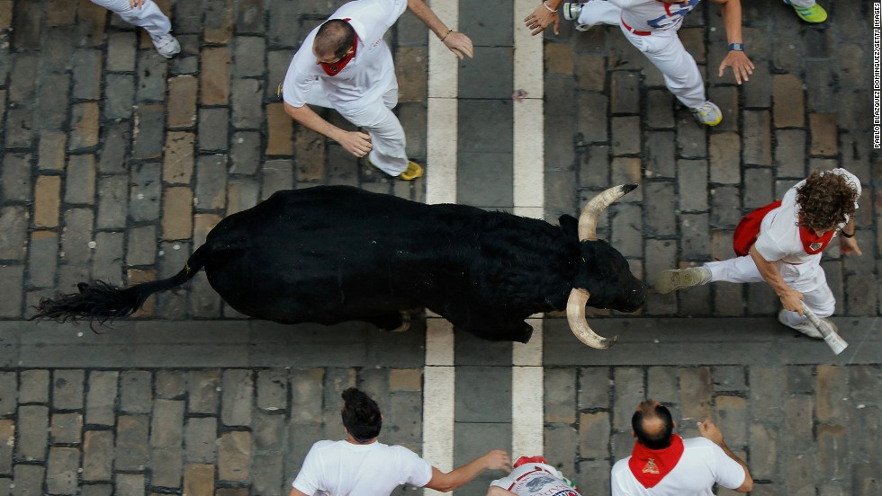 Participants run alongside a fighting bull in Pamplona on July 9.