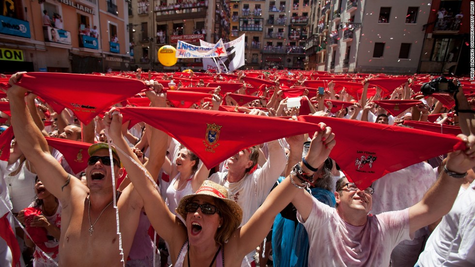 People hold up their red handkerchiefs during the opening ceremony on July 6.