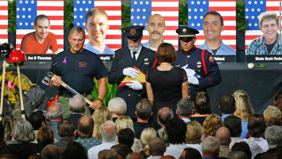 "An honor guard presents a family member with an American flag during a memorial service in Prescott Valley, Arizona, on Tuesday, July 9. <a href=""http://www.cnn.com/interactive/2013/07/us/yarnell-fire/index.html"">Nineteen members of the Granite Mountain Hotshots</a> died Sunday, June 30, battling the Yarnell Hill wildfire."