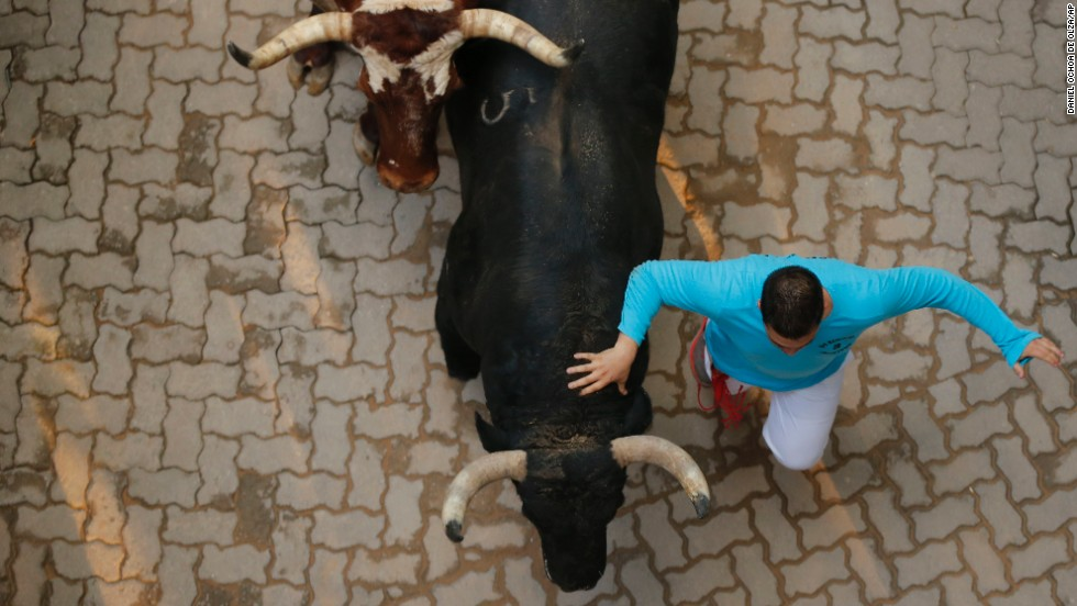 "Two fighting bulls run next to a participant on July 12. The annual festival was popularized by Ernest Hemingway's 1926 novel ""The Sun Also Rises."""