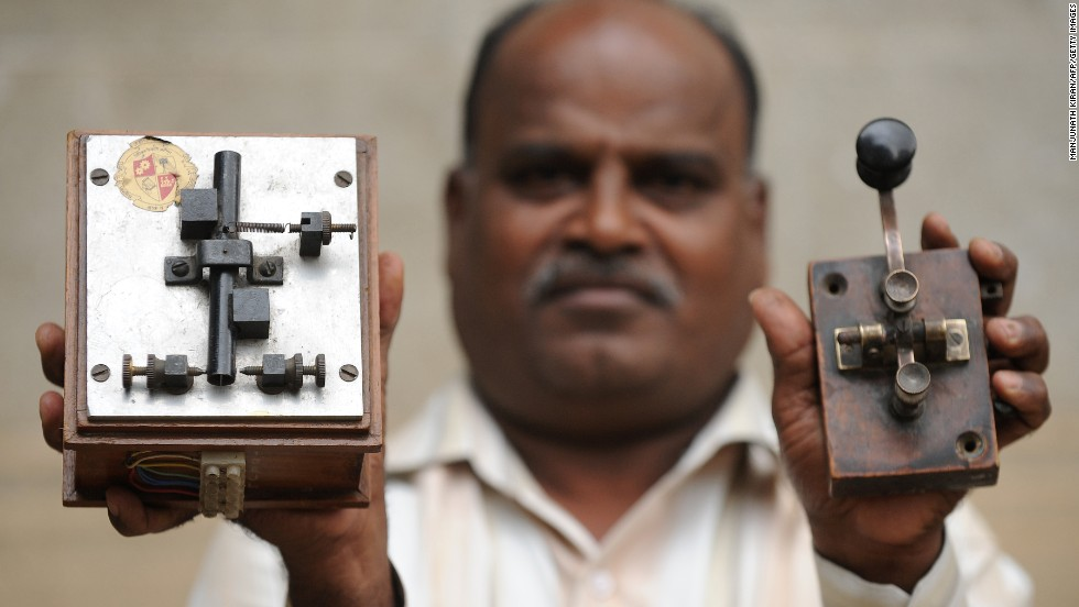An employee displays an antique telegraph transmitter key (right), which the operator used to send messages via Morse Code, and a telegraph receiver (left).