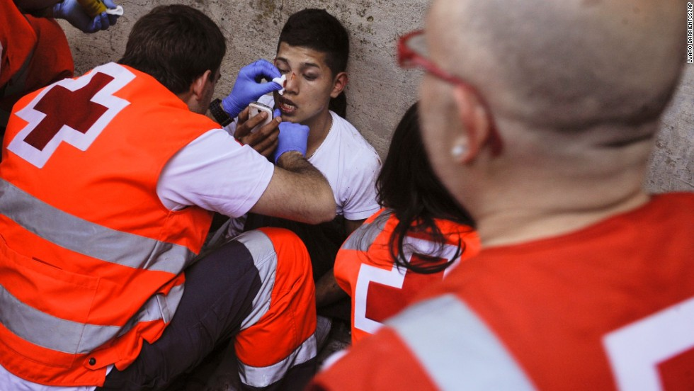 An injured man receives medical attention outside of the bull ring on July 13.