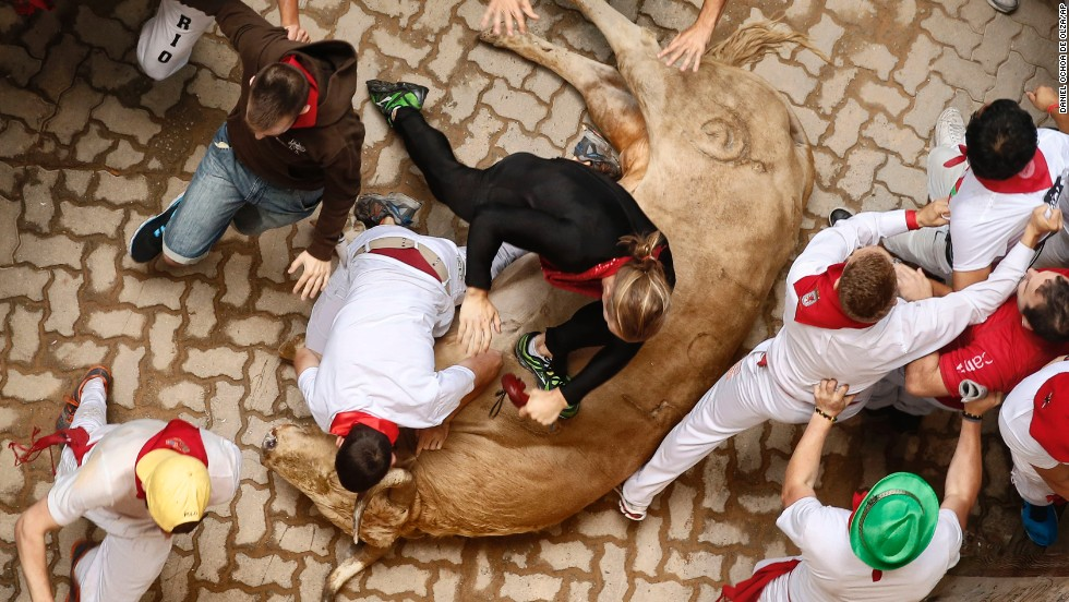 Runners stumble and trip over a fallen bull on July 13.