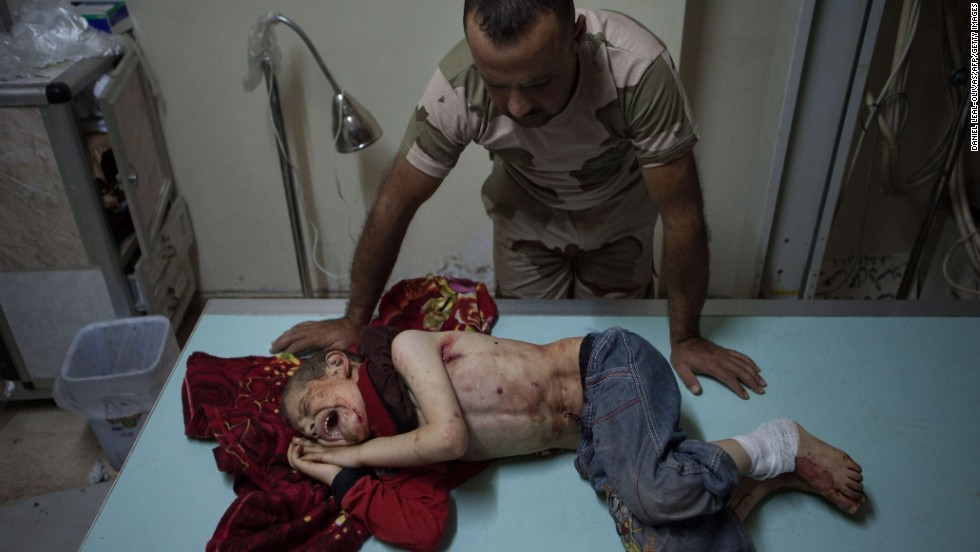 A Free Syrian Army fighter stands over a boy who was injured during shelling in Al-Bara on Monday, July 8.