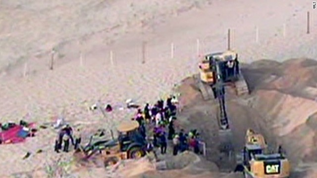 Rescuers work after a sand dune swallows a 6-year-old boy.