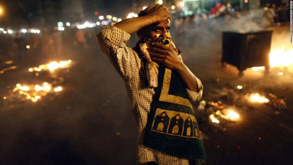 A supporter of the Muslim Brotherhood and of Morsy covers his mouth under the 6th October Bridge in Cairo on Tuesday, July 16.