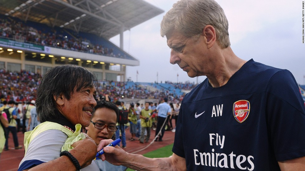 English Premier League football team Arsenal spent three days in Hanoi as part of its Asian tour. The team's manager Arsene Wenger signs a local photographer's t-shirt during a training sesssion at Hanoi's My Dinh stadium.
