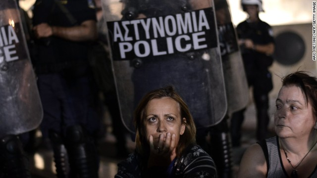 A demonstrator reacts in front of riot police as lawmakers prepared to vote on a controversial  reform involving a shake-up of civil service on Tuesday July 17.