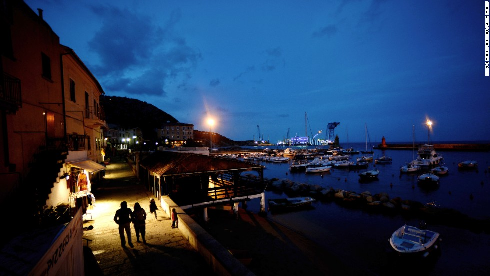 A couple walks along the port of Giglio at night on January 12, 2013.