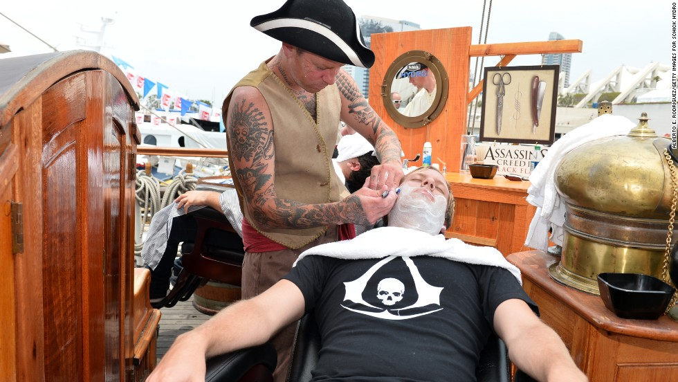 Barbers dressed as pirates shave customers at the Assassin's Creed IV Black Flag Jackdaw Ship on July 20.